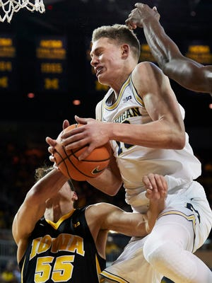 Feb 14, 2018; Ann Arbor, MI, USA; Michigan's Moritz Wagner grabs the rebound over Iowa's Luka Garza in the first half at Crisler Center.