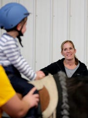 Melanie Roerdink washes as her son Beckett rides Maverick