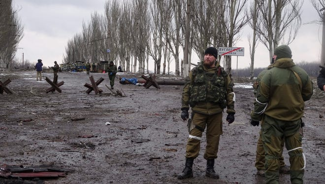 Pro-Russian rebels stand near a seized checkpoint near Debaltseve, in the Donetsk area of eastern Ukraine on Wednesday, Feb. 4, 2015. The European Union has demanded an immediate ceasefire around the transport hub under the separatists' attack.