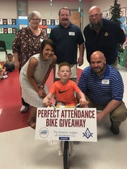 Rick Curby, center back, and Mike Austin, at right in back, pose with bike winner Elijah Mabrey at the Thelma B. Johnson Early Education Center.