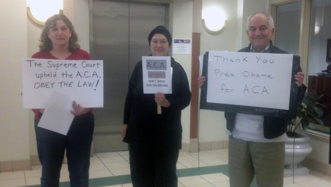 Members of the Warren County Democratic Party protest an announcement made Monday by Ohio Attorney General Mike Dewine and GOP officials from Warren County that the state and county has filed a lawsuit challenging a key provision of the Affordable Care Act.  From left: Sarah Davis, Gale Roberts and Rob Weidenfeld.