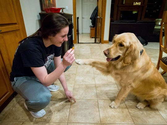 Caitlin Clark gives a treat to the family golden retriever