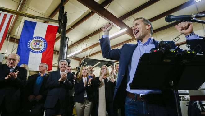"""Then-Missouri Gov. Eric Greitens cheers on a crowd after several protesters were removed from the building before a ceremonial signing making Missouri a """"right-to-work"""" state at the abandoned Amelex warehouse in Springfield, Mo. on Monday, Feb. 6, 2017."""