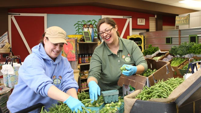 Nicole Converse and Melissa Tabalno share a laugh as they prepared for Saturday's opening of Veggie Pails at 2221 East Highland Road.
