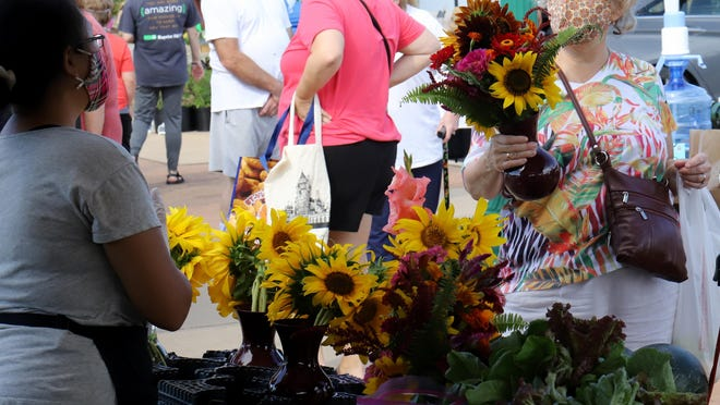 Alison Kotarek of Greenwood picks up a fresh bouquet of flowers, Saturday, August 1, 2020, during a morning shopping trip to the Fort Smith Downtown Farmer's Market.