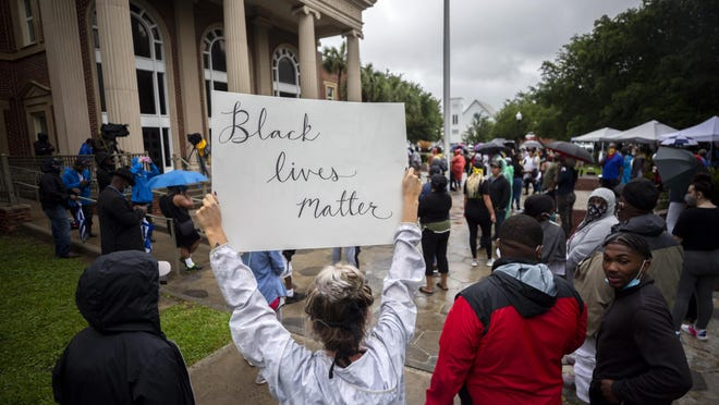A group of protesters gather outside the Glynn County Courthouse while a preliminary hearing is being held inside for for Travis McMichael, Gregory McMichael and William Bryan, Thursday, June 4, 2020, in Brunswick, Ga. The three are accused of shooting of Ahmaud Arbery while he ran through their neighborhood in February.