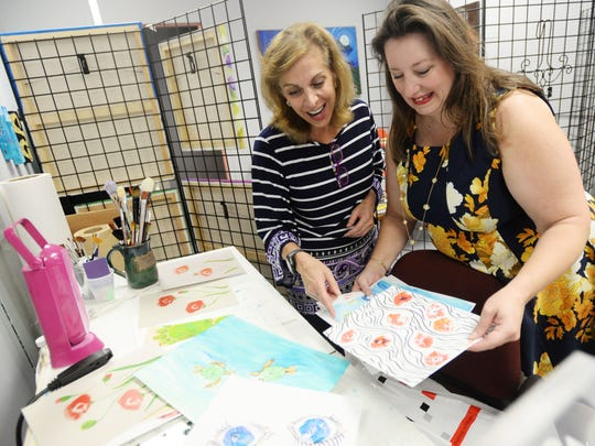 Artist Lynn Laird, right, shows her client Victoria Provenza the artwork she made for her from paint impressions from Provenza's breasts before a masectomy.