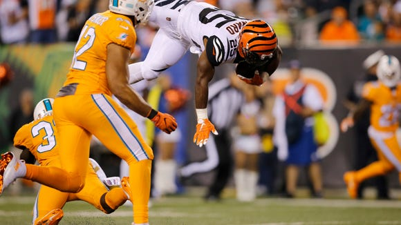 Cincinnati Bengals running back Giovani Bernard (25) is upended on a reception in the third quarter of the NFL Week 4 game between the Cincinnati Bengals and the Miami Dolphins at Paul Brown Stadium on Thursday, Sept. 29, 2016. The Bengals improved to 2-2 with a 22-7 win over the Dolphins.