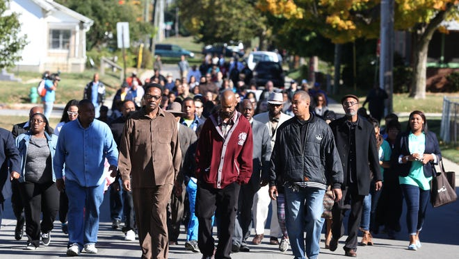 People march during a peace rally at Tarkington Park Sunday October 18, 2015. Faith leaders and members of the community came out to rally and march in the name of peace after a rash of recent killings in the area.