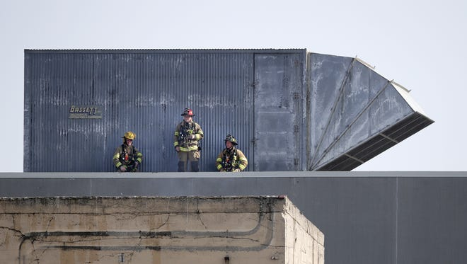 Firefighters took to the roof of the U.S. Paper Mills Corp. building in Menasha on Thursday afternoon as they fought a fire that began in one of the paper machines.