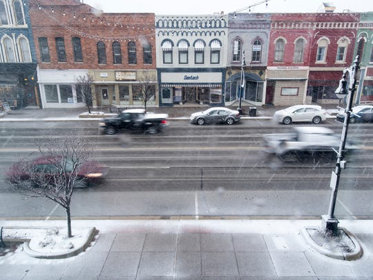 Vehicles drive down Military Street in the snow March
