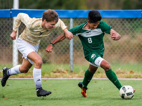 Indian River's Mikie Mochiam (No. 8) cuts into the box as Salesianum's Taylor Witherell (No. 7) tries to hold him back in the second half of Salesianum's 3-2 overtime win over Indian River High School at the Hockessin Soccer Club in Hockessin on Tuesday afternoon.