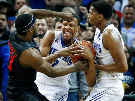 University of Memphis forward Jimario Rivers (middle) grabs a rebound away from teammate Dedric Lawson (right) and SMU forward Ben Emelogu II (left) during second-half action at the FedExForum.