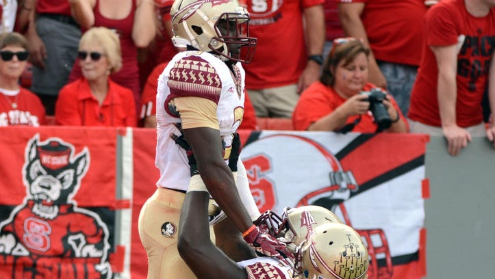 Sep 27, 2014; Raleigh, NC, USA; Florida State Seminoles reciever Jesus Wilson (3) is held up by offensive lineman Cameron Erving (75) after scoring a touchdown during the first half against the North Carolina State Wolfpack at Carter Finley Stadium. Mandatory Credit: Rob Kinnan-USA Today Sports
