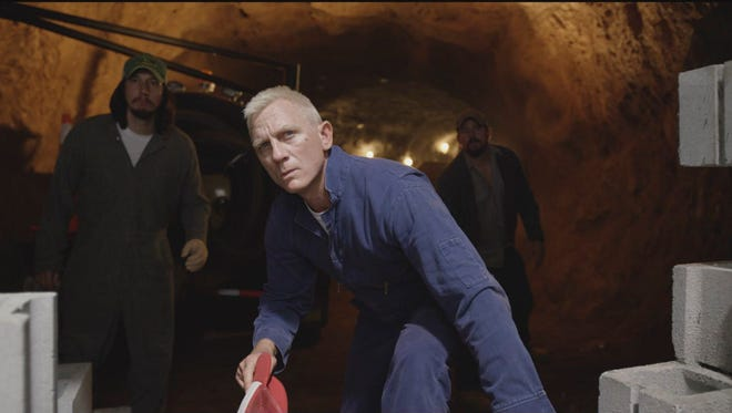 """Daniel Craig (center, with Adam Driver at left and Channing Tatum at right in the dimly lit background) stir up trouble in Steven Soderbergh's """"Logan Lucky."""""""