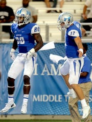 MTSU's Ed Batties (80) left, and quarterback Brent Stockstill (12), right jump in the air to celebrate Batties' touchdown in first half of an NCAA college football game against Jackson State, on Saturday, Sept. 5, 2014, in Murfreesboro, Tenn.