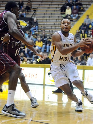 The University of Southern Mississippi's Shadell Millinghaus drives to the basket while being guarded by Troy defenders during their game Tuesday night at USM's Reed Green Coliseum.