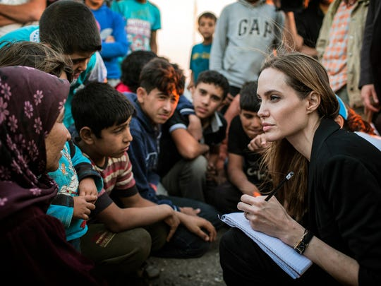 In this 2013 photograph, Angelina Jolie takes notes
