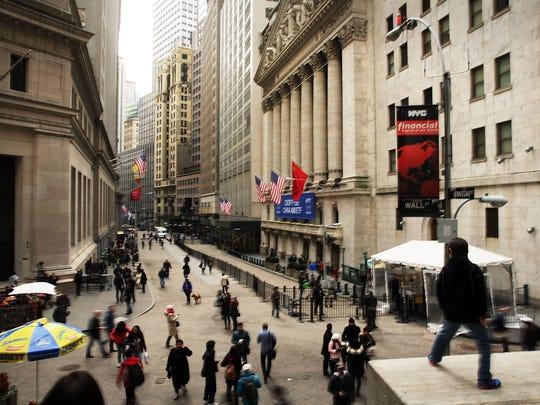 People walk through lower Manhattan past the New York