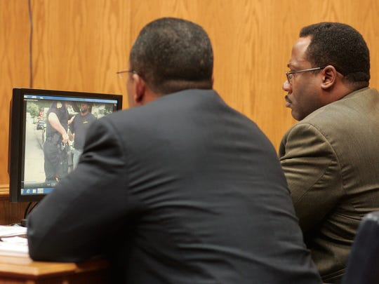 Steven Smith, right, owner of Big Momma's in Newark, charged with first degree felony possession and trafficking in cocaine, watches as his arrest video captured by a patrol car is displayed on a monitor Tuesday afternoon.