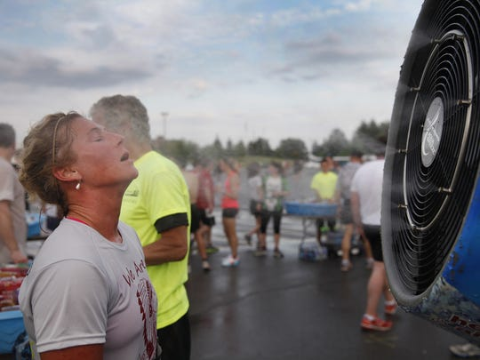 A runner stands in front of a cooling fan after finishing the Chase Corporate Challenge at RIT.