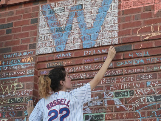 Chicago Cubs fan Rahaf Rihani chalks a message on a wall outside Wrigley Field the day after the Cubs defeated the Cleveland Indians to win the 2016 World Series on November 3, 2016 in Chicago, Illinois. The Cubs 8-7 extra-inning win in game seven landed them their first World Series title since 1908.