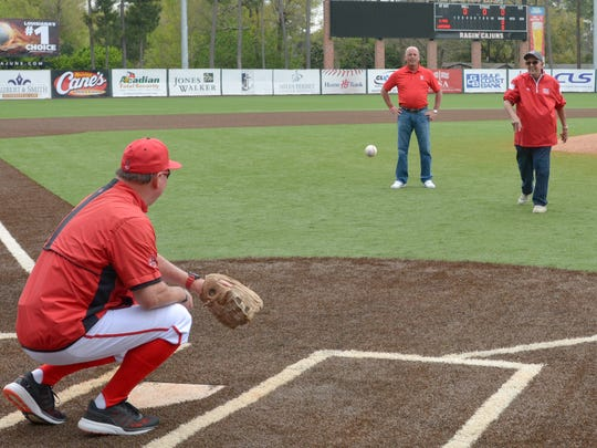 Ray Robicheaux throws out the first pitch to his son, UL coach Tony Robicheaux, as Chris Russo watches before the Cajuns beat Southern Miss on Saturday at Tigue Moore Field at Russo Park.