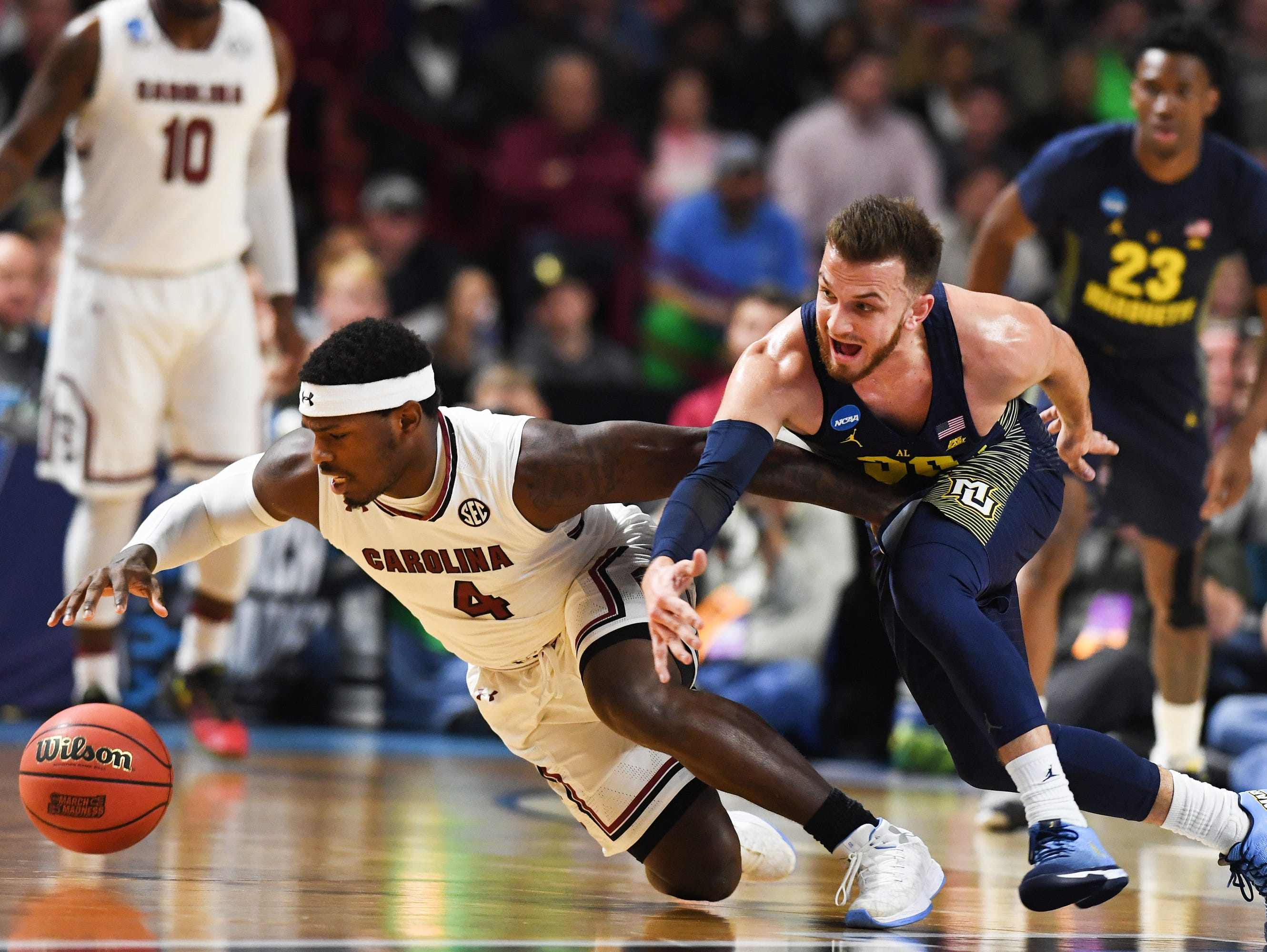 South Carolina guard Rakym Felder (4) and Marquette guard Andrew Rowsey (30) try to gain control of the ball during the 1st round of the NCAA Tournament at Bon Secours Wellness Arena in downtown Greenville on Friday, March 17, 2017.