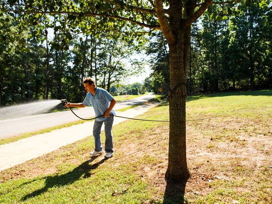 """Jim Lankford waters his lawn on Wednesday, June 6, 2018. Lankford says his chronic pain prevents him from being as active as he would like, but he still works outside partly because he says he cannot afford to hire outside help. """"It just takes me a lot longer to do the work now,"""" Lankford says. """"What used to take me a day now takes me several days."""""""