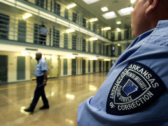 Guards patrol a cell block housing disruptive inmates