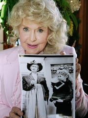 "In this Jan. 8, 2009 photo, Donna Douglas, who starred in the television series ""The Beverly Hillbillies,"" holds a publicity picture of herself from the show, in Baton Rouge, La. Douglas played the buxom tomboy Elly May Clampett."