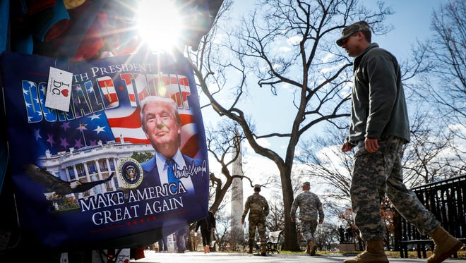 Military personnel walk along the National Mall in Washington on Jan. 18, 2017, alongside vendors selling President-elect Donald Trump merchandise ahead of Friday's presidential inauguration.