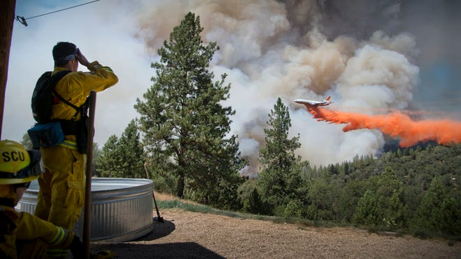 A DC-10 Air Tanker makes a drop on the Sand Fire at the middle fork of the Cosumnes River in Northern California as firefighters standby to protect a home on Saturday, July 26, 2014.