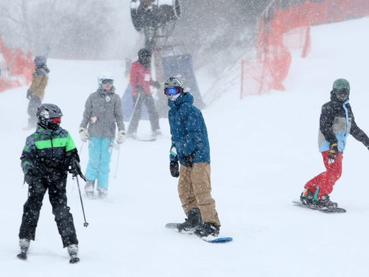 Skiers and snowboarders enjoy the fresh fallen snow