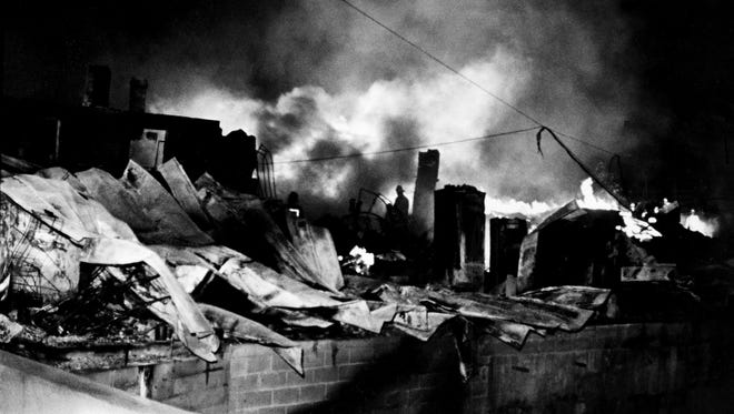 A fireman, center, can barely be seen standing in the midst of a building Feb. 24, 1978, that was destroyed after a propane tanker car of a derailed L&N freight train exploded in downtown Waverly, Tenn.