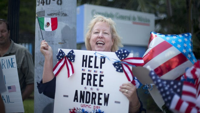 Jill Tahmooressi stands outside the Mexican Consulate in Miami, Monday, May 5, 2014, protesting the arrest of her son in Mexico. Andrew Tahmooressi, a Marine veteran who was arrested and jailed in Mexico on weapons charges for allegedly bringing guns across the border, says he never intended to leave the country but missed an exit when heading to meet friends in a border town. He told the newspaper that Mexican authorities found three guns inside the truck he had recently driven across the country to make a new start in San Diego. (AP Photo/J Pat Carter)