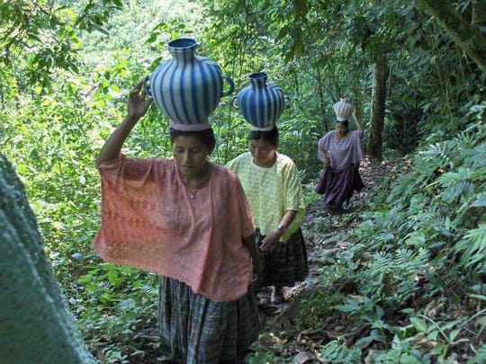 Ladies carry water jugs on their heads as they make the journey back to the village.