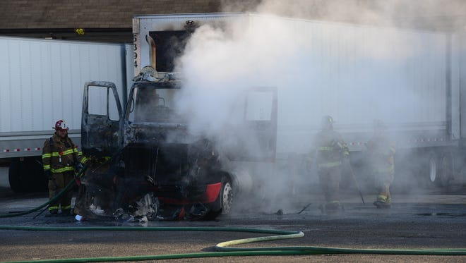 Firefighters check the tractor-trailer cab that caught fire at a Soundview Paper Co. storage facility on East 54th Street on Elmwood Park Thursday morning.