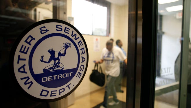 Detroit Water and Sewerage Department logo is displayed on a window as customers attend a Water Affordability Fair in 2014.