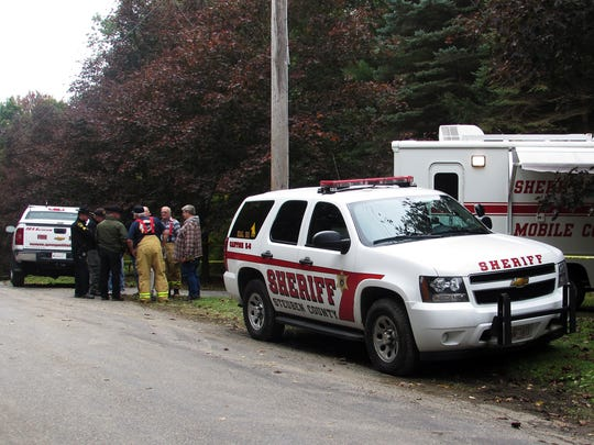 Steuben County sheriff's deputies and volunteer firefighters gather Oct. 1 in front of the Thomas and Kelley Clayton home  in Caton.