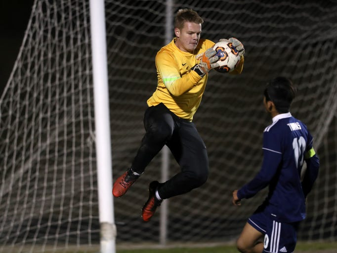 Florida High's Hayden Farrell snags a shot on goal