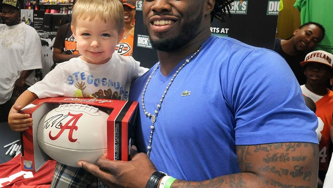 Wyatt Stearns,2, poses for a photo with NFL star Trent Richardson Saturday at Dick's Sporting Goods.