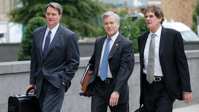 File photo of former Virginia Gov. Bob McDonnell, center, when he arrived at federal court with his attorneys, John Brownlee, left, and Henry Asbill, right, in Richmond, Va., Monday, Aug. 18, 2014.