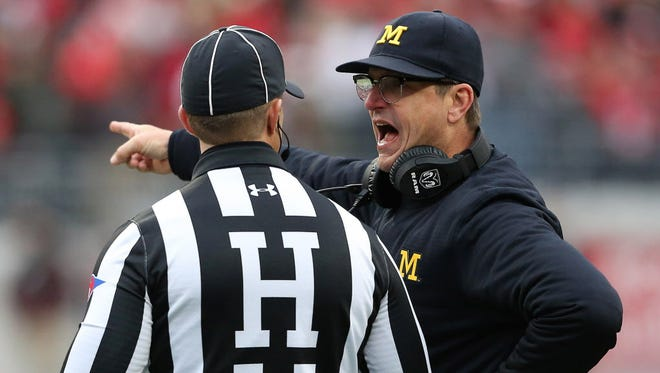 Michigan head coach Jim Harbaugh discusses a call with the referee during the third quarter of the Wolverines' game against Ohio State.