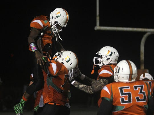 Dunbar players celebrate Seneca Millidge's punt return for a touchdown in the 5A-3 regional semifinal game at Dunbar High School on Friday, November 20, 2015.