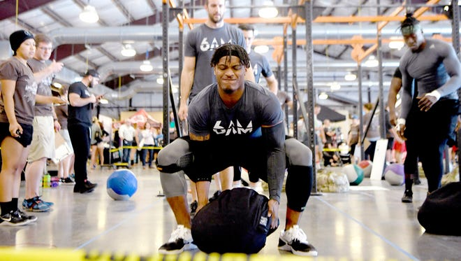 London Richardson, of Summit CrossFit's 6AM team, lifts a 135-pound Brute Ball to throw over his shoulder while competing during The Appalachian Games hosted by Summit CrossFit at the WNC Agricultural Center on Saturday, April 14, 2018.