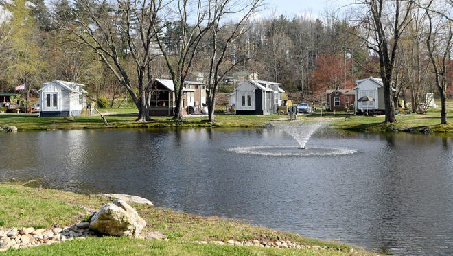 A pond with a fountain is surrounded by home at The Village at Flat Rock on Tuesday, April 3, 2018. The community is made up of more than 110 tiny homes and is growing and improving.