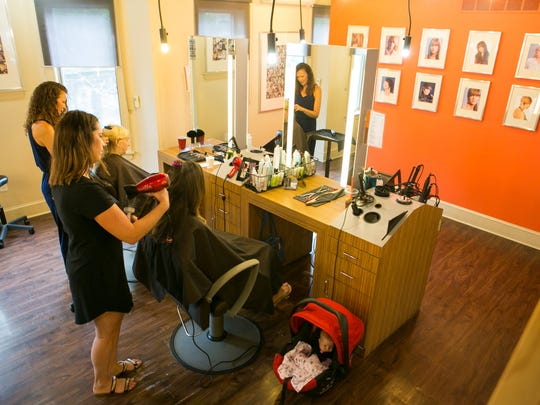 Stylists Carmen Negron (from left) and Allison McNicholas work on customers at Fabrizio Salon & Spa in Wilmington.