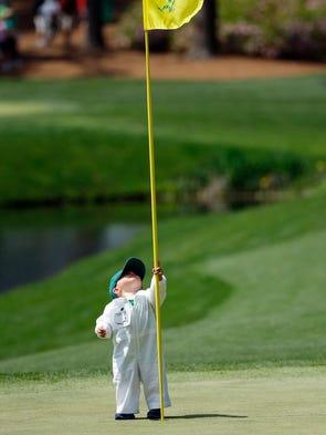 Scott Stallings's son Finn surveys a flagstick at Augusta National.