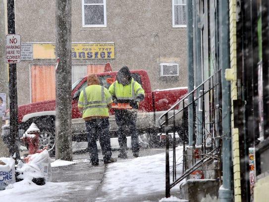 2:01 p.m. Workers put salt down in the sidewalks in